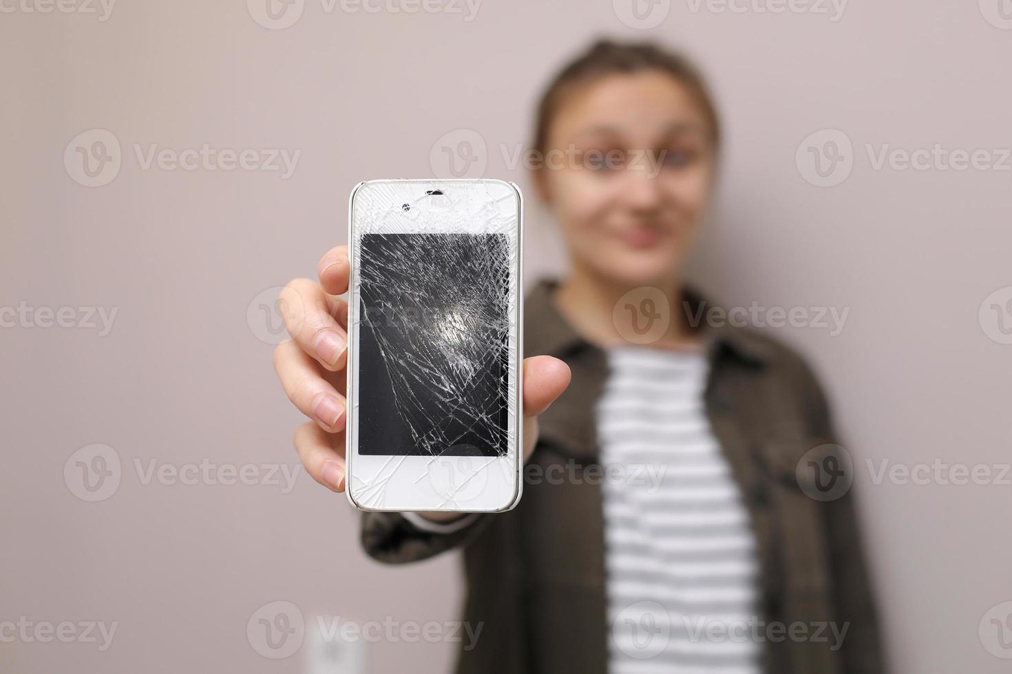 jeune femme frustrée tenant un téléphone portable avec une vitre d'écran cassée. l'écran du téléphone doit être réparé. isolé sur fond gris. mise au point sélective sur smartphone photo