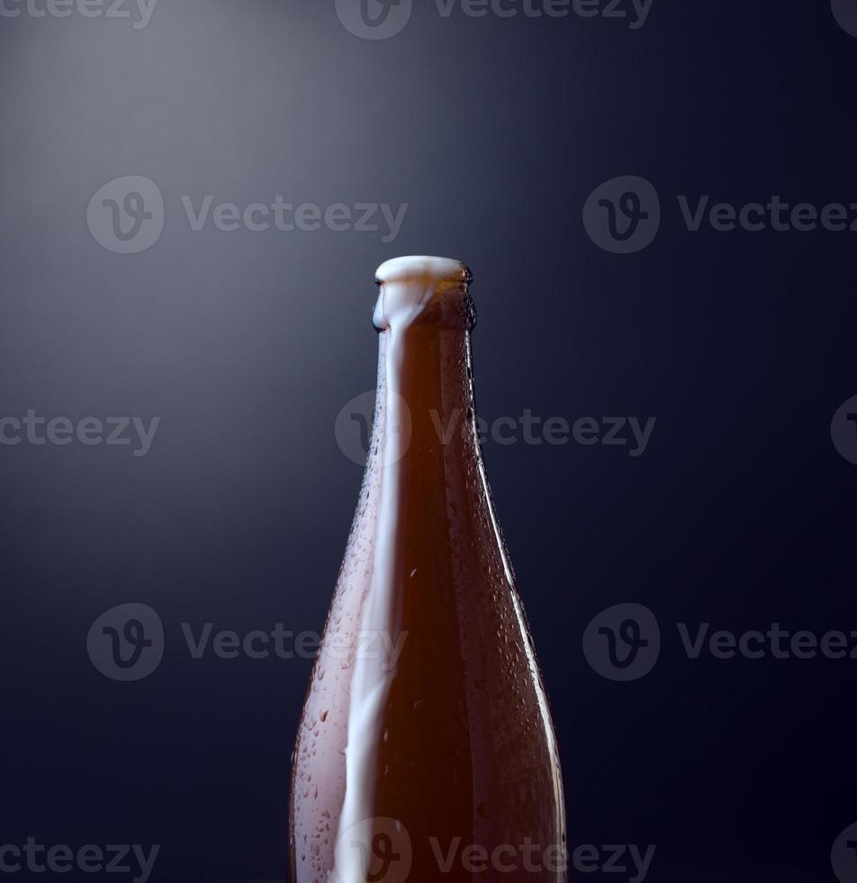 vue de face d'une bouteille de bière froide avec de la mousse débordante sur fond bleu grunge vintage. photographie organique, style d'image vertical, carré. photo