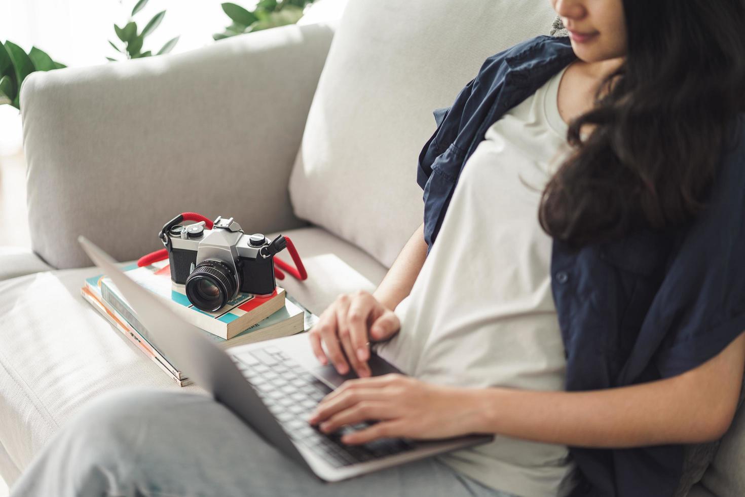 photographe asiatique assise sur le canapé à l'aide de l'ordinateur portable pour travailler avec un appareil photo reflex à la maison, concept d'employé créatif et indépendant.