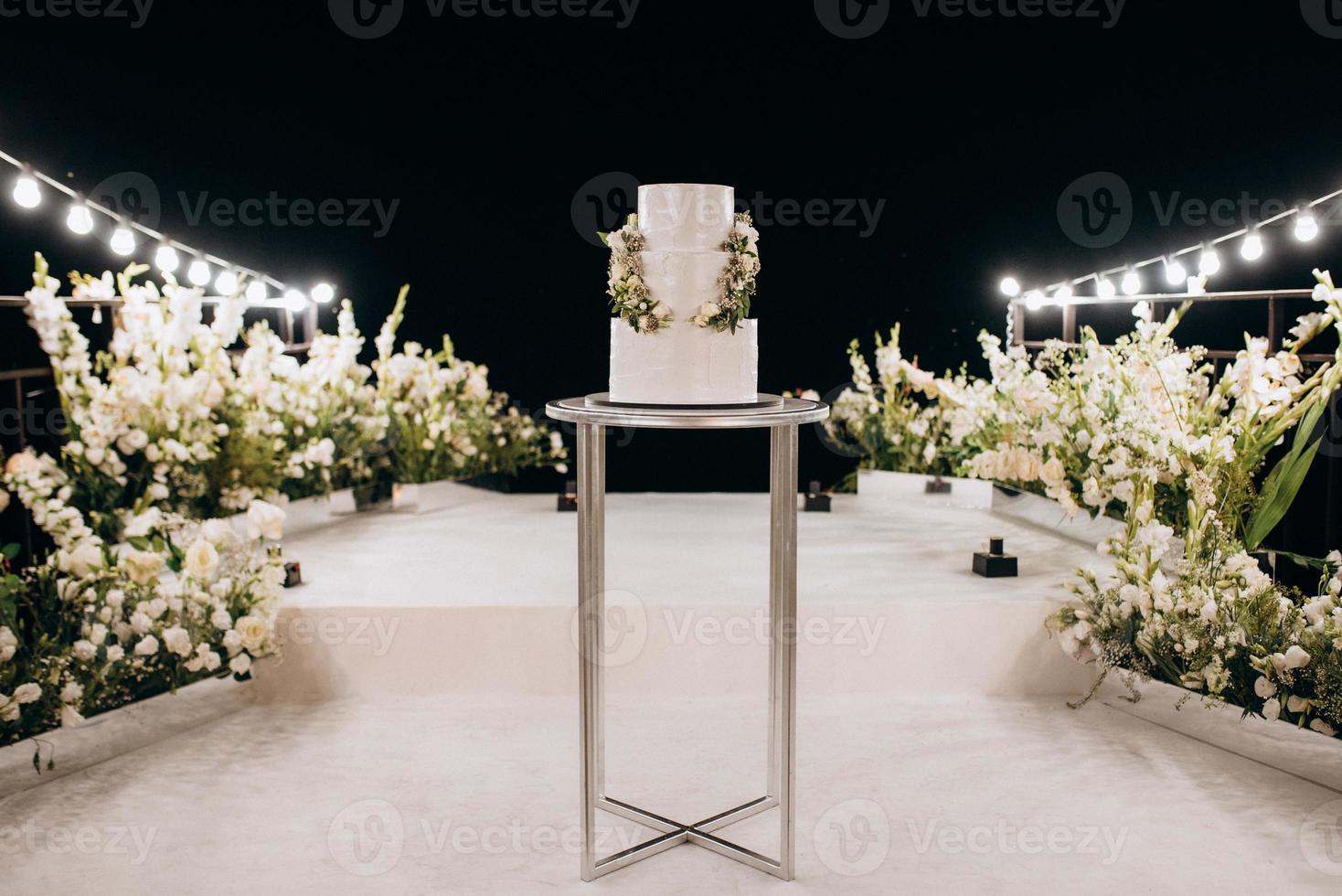 gâteau blanc de mariage sur un stand élevé près du podium blanc photo