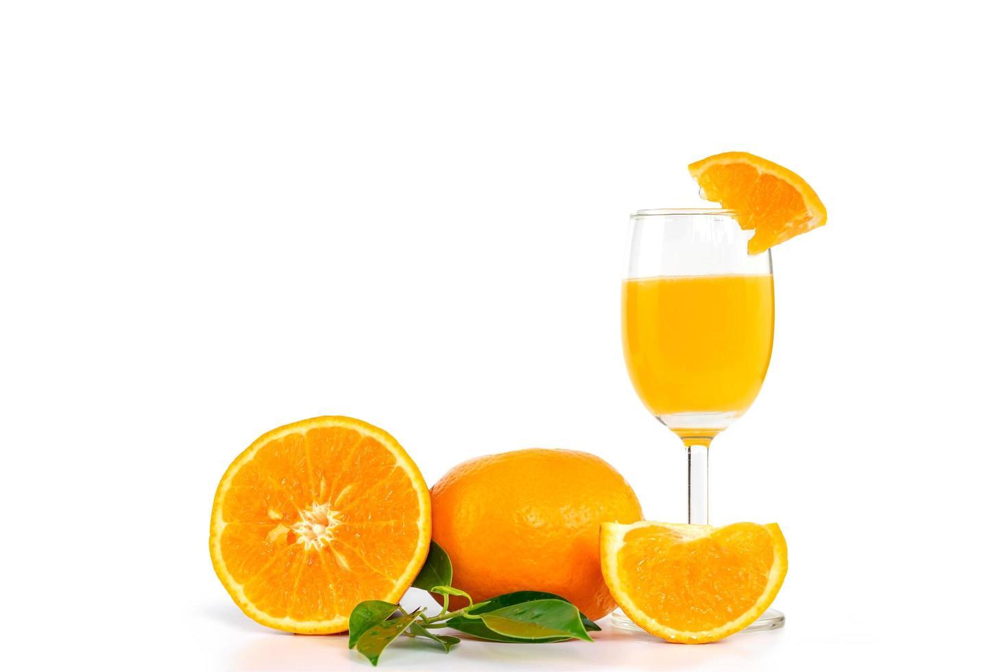 jus d'orange fraîchement pressé dans un verre, décoré d'agrumes et de feuilles d'oranger photo