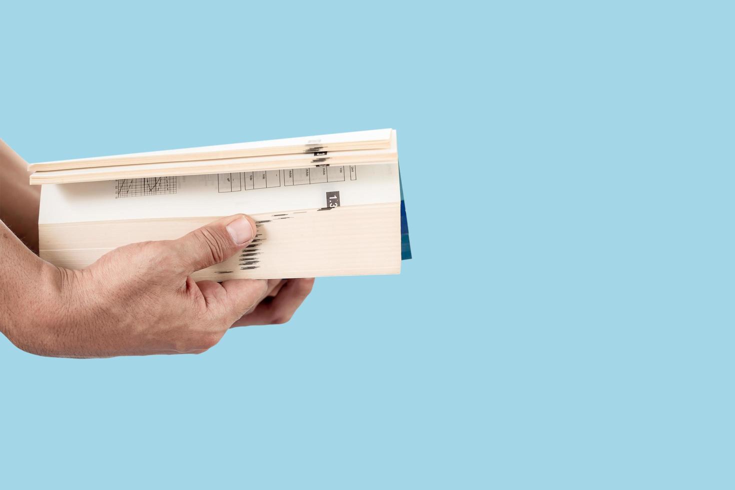 main de l'homme tenant et ouvrant un livre épais isolé sur fond de couleur pastel bleu photo