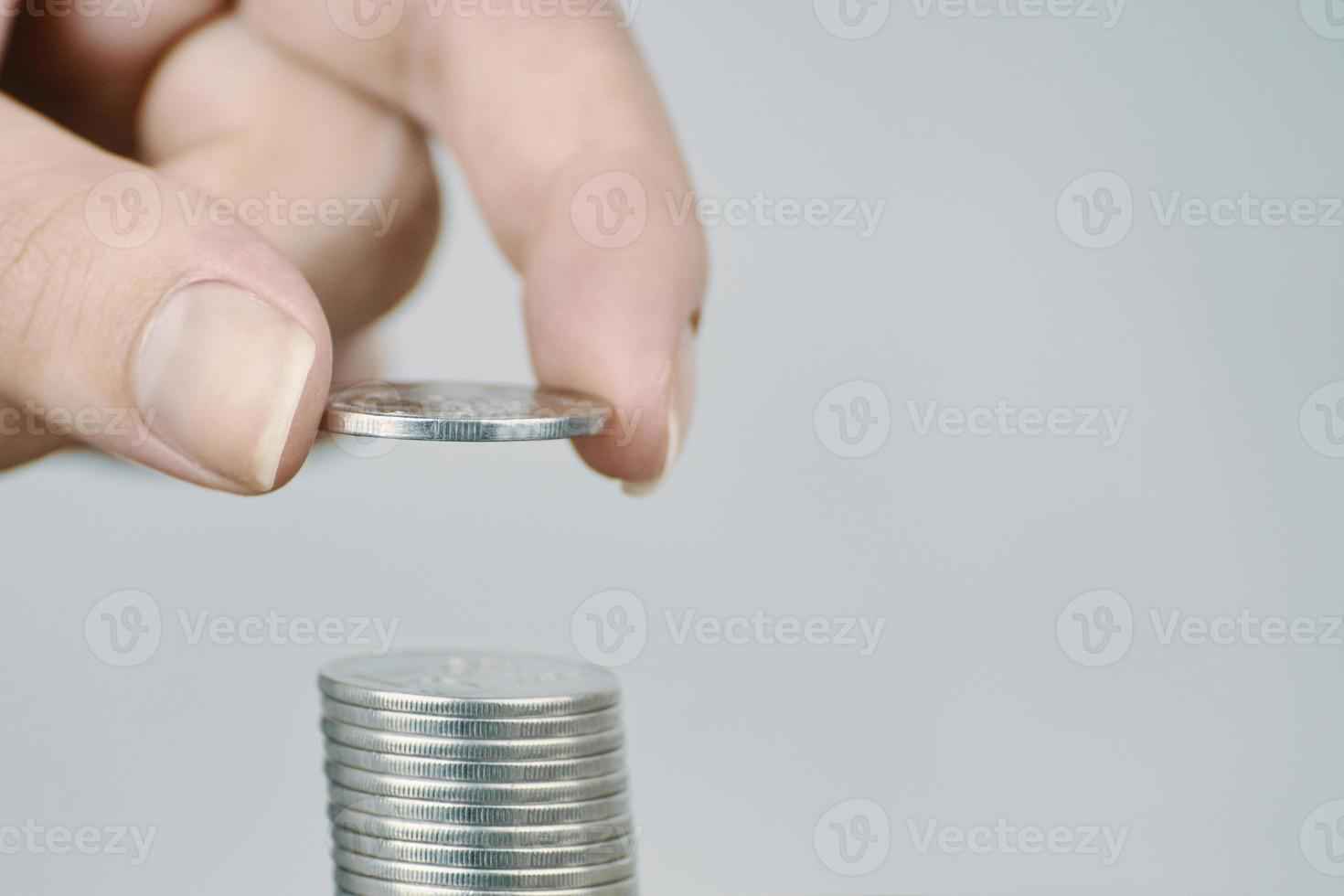 la main de la femme a mis des pièces d'argent en argent à empiler. photo