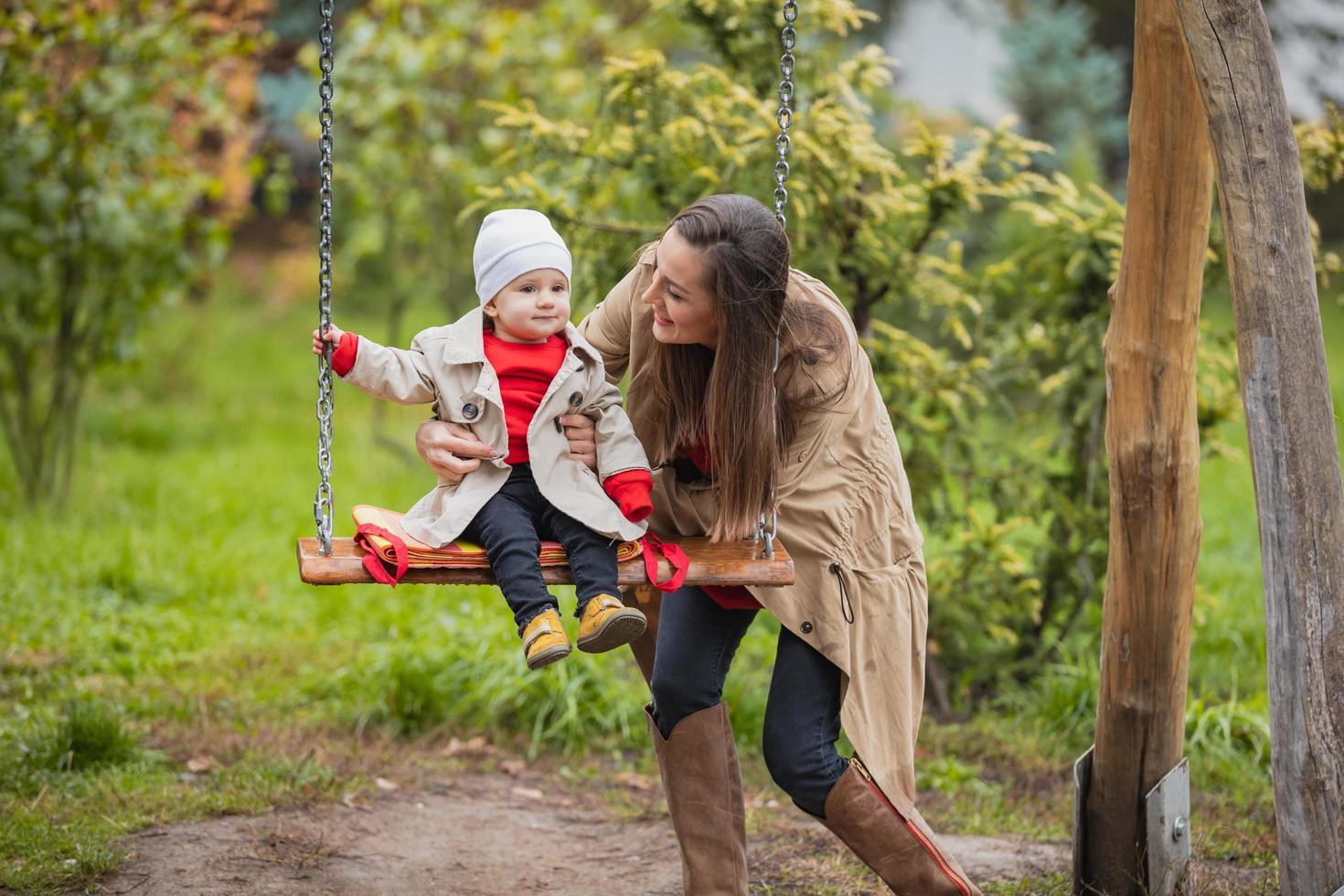 la mère secoue son bébé sur la balançoire au parc d'automne. famille heureuse passer du temps ensemble. photo