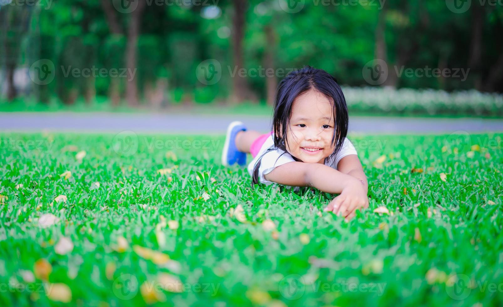petite fille asiatique allongée sur le sol et regardant quelque chose photo