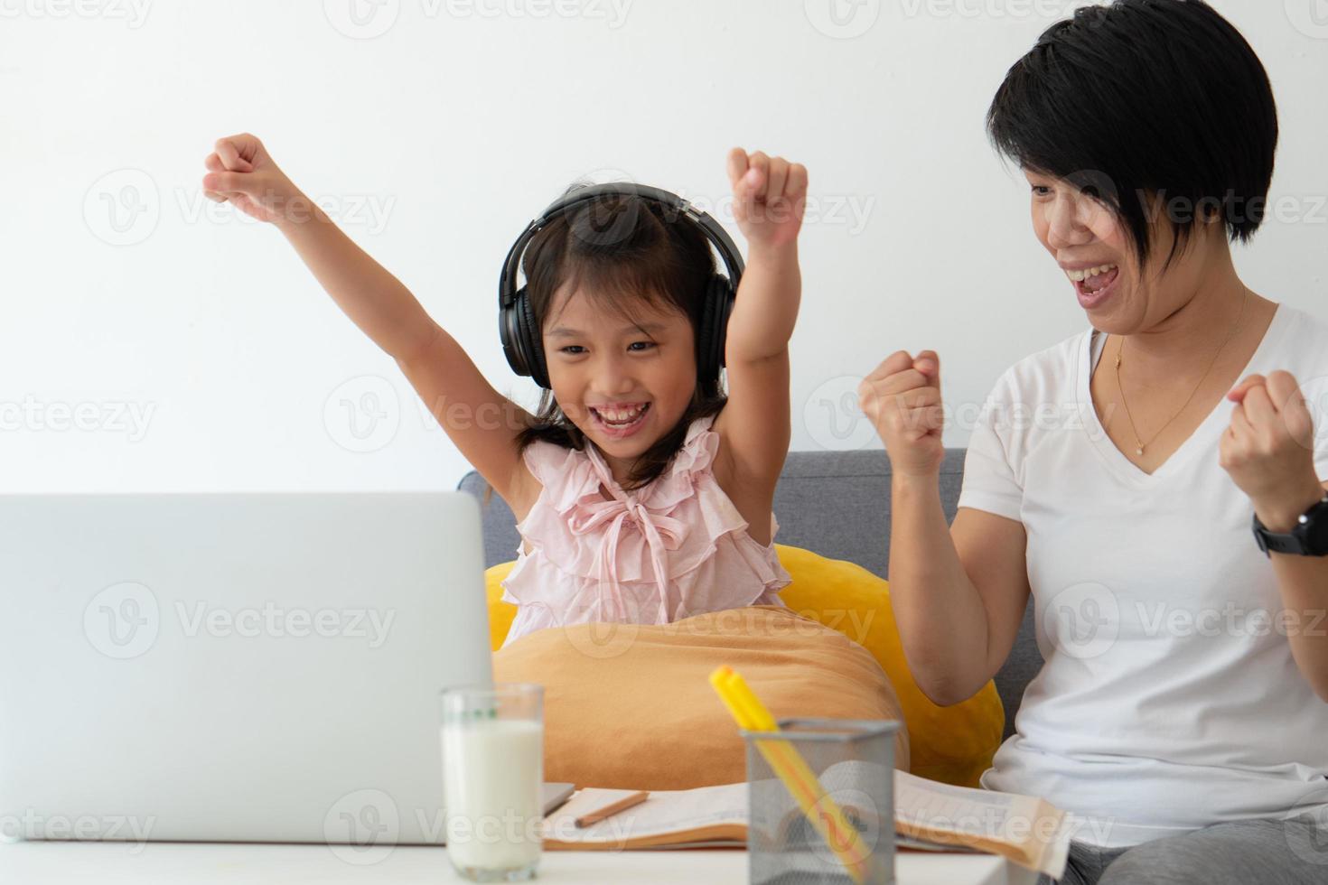 une mère asiatique enseigne à une jeune fille de la leçon d'informatique en ligne comme enseignement à domicile en raison d'une épidémie de covid-19 ou de coronavirus photo