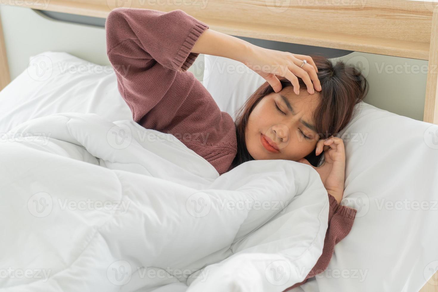 femme asiatique avec maux de tête et dormir sur le lit photo