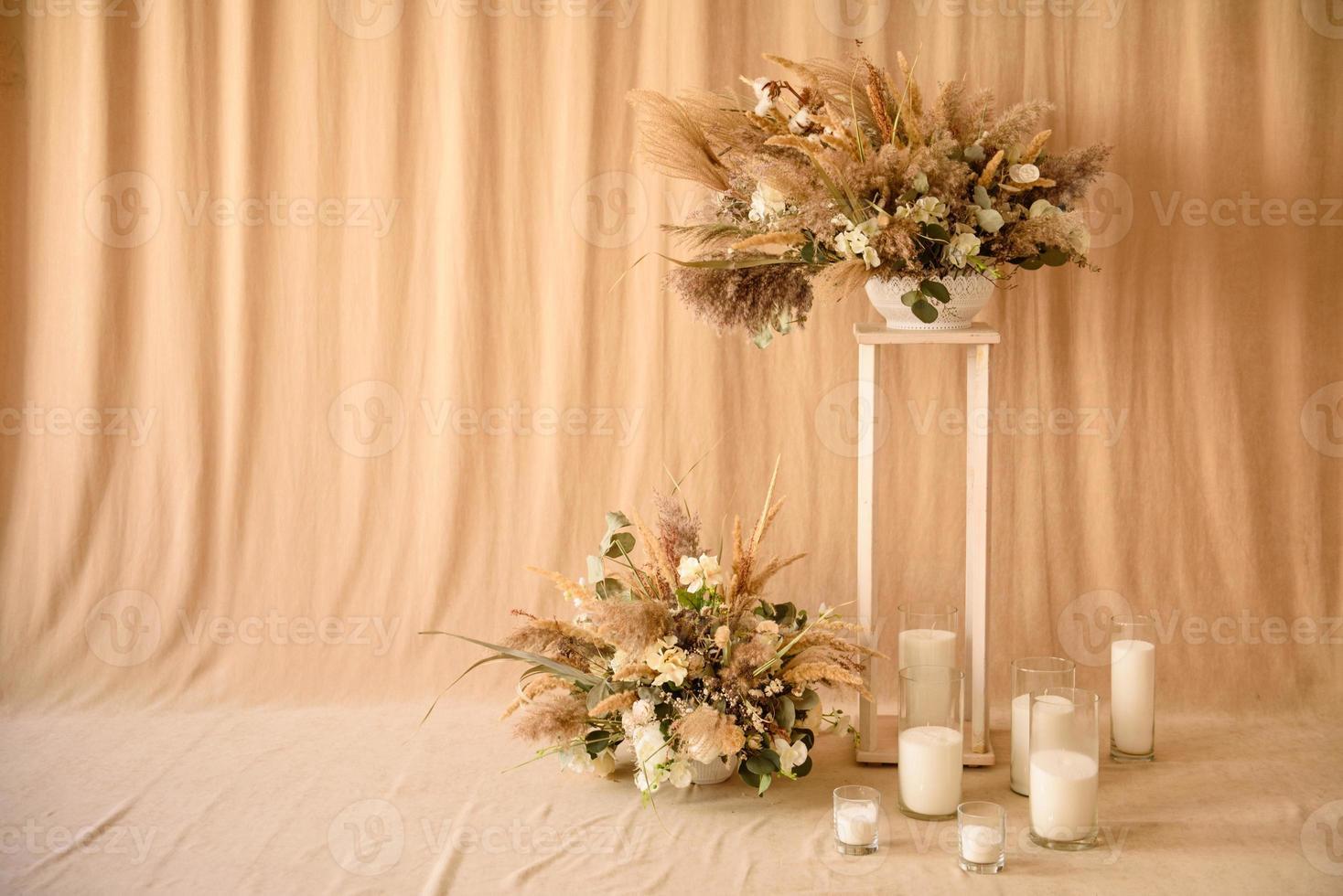 décorations de belles fleurs sèches dans un vase blanc sur fond de tissu beige photo
