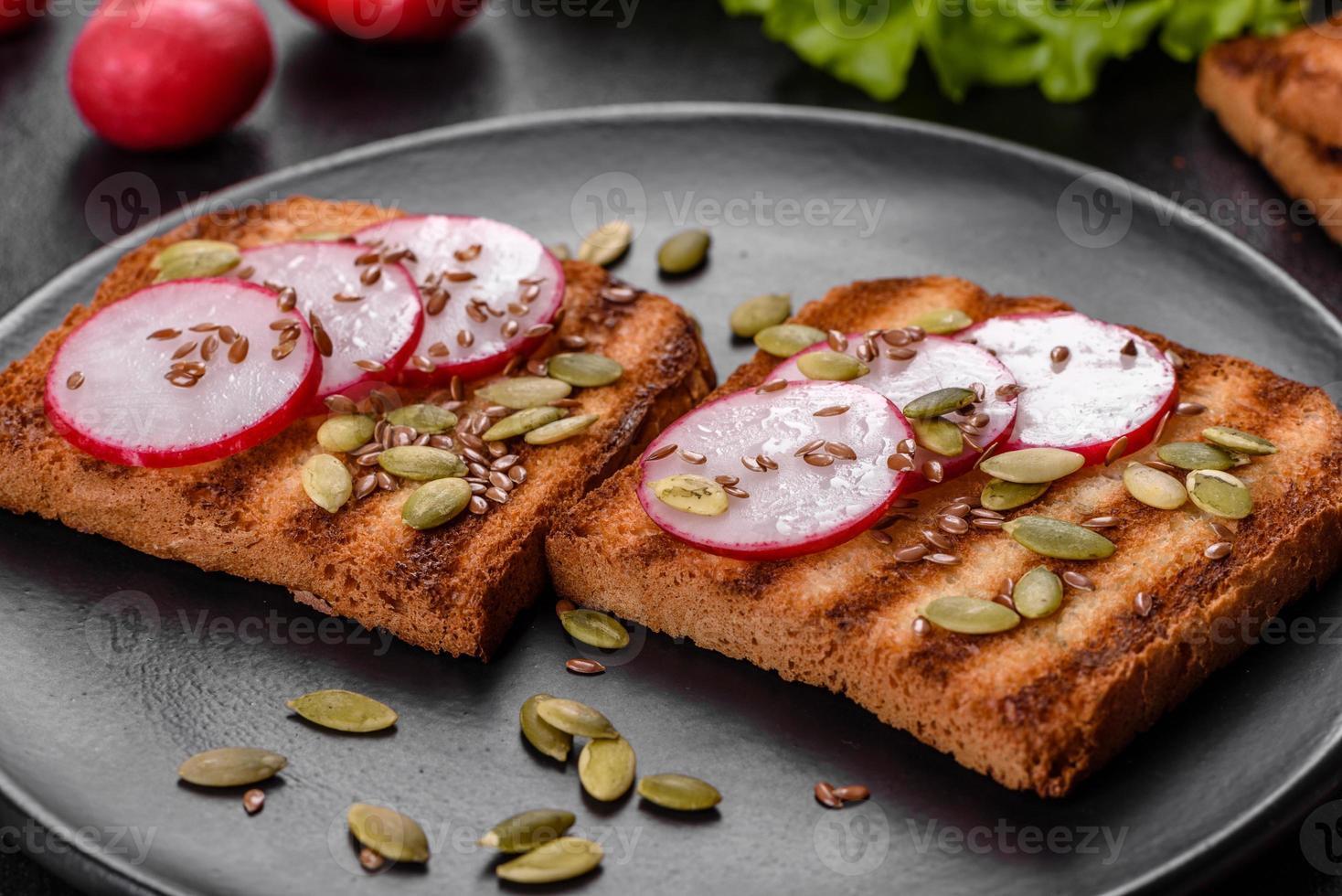 délicieux sandwich croustillant avec pain grillé, radis, graines de citrouille et graines de lin photo