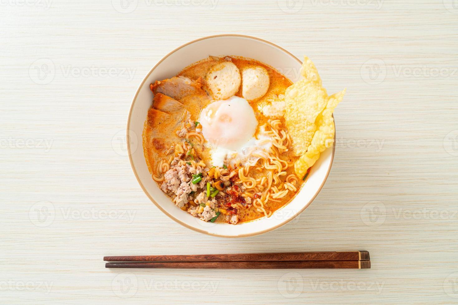 nouilles instantanées au porc et boulettes de viande dans une soupe épicée ou nouilles tom yum à l'asiatique photo