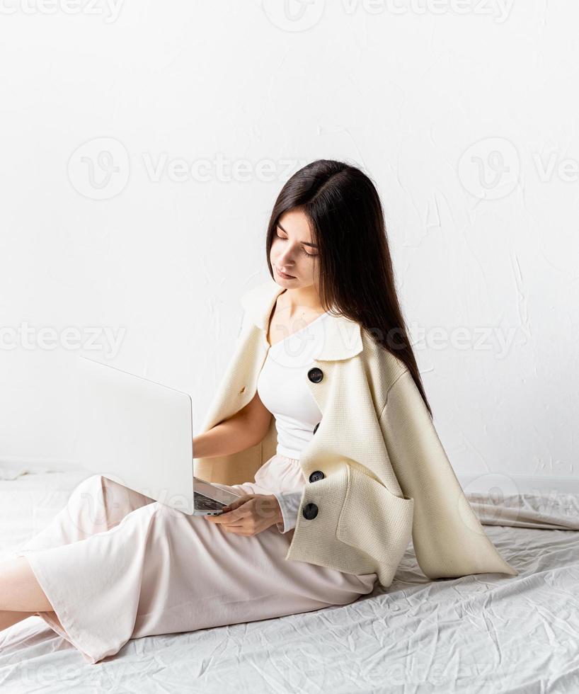 femme assise sur le sol et faisant un projet indépendant sur un ordinateur portable photo
