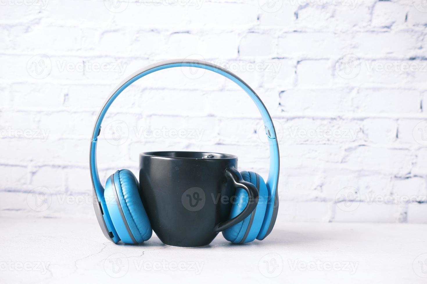 tasse à café de couleur noire et un casque sur la table photo