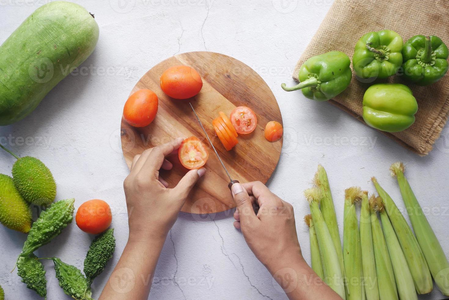 main de personne coupant des tomates sur une planche à découper photo
