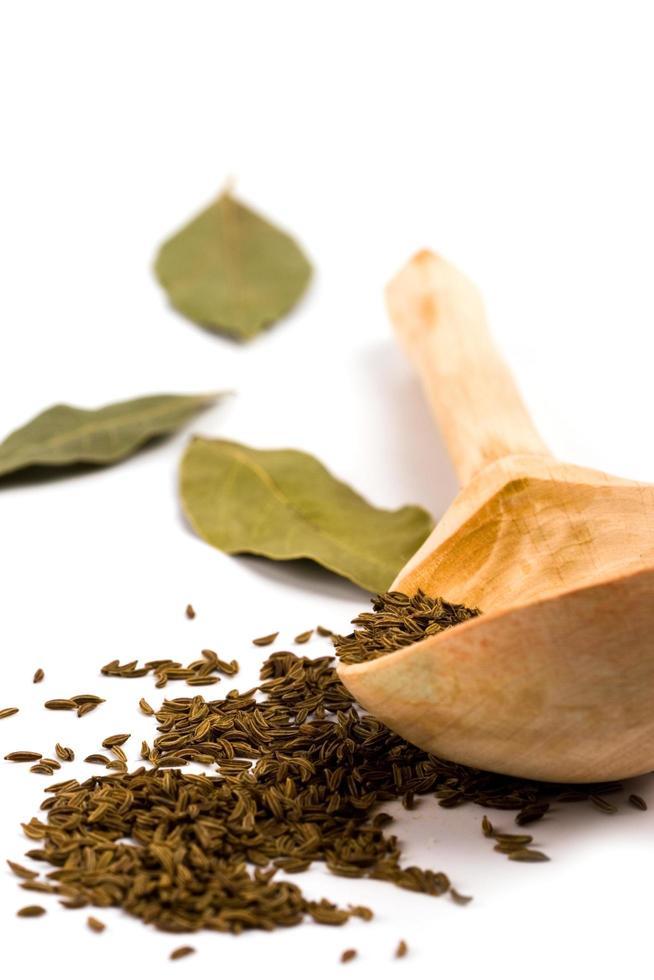 cumin sur cuillère en bois et feuilles de laurier photo