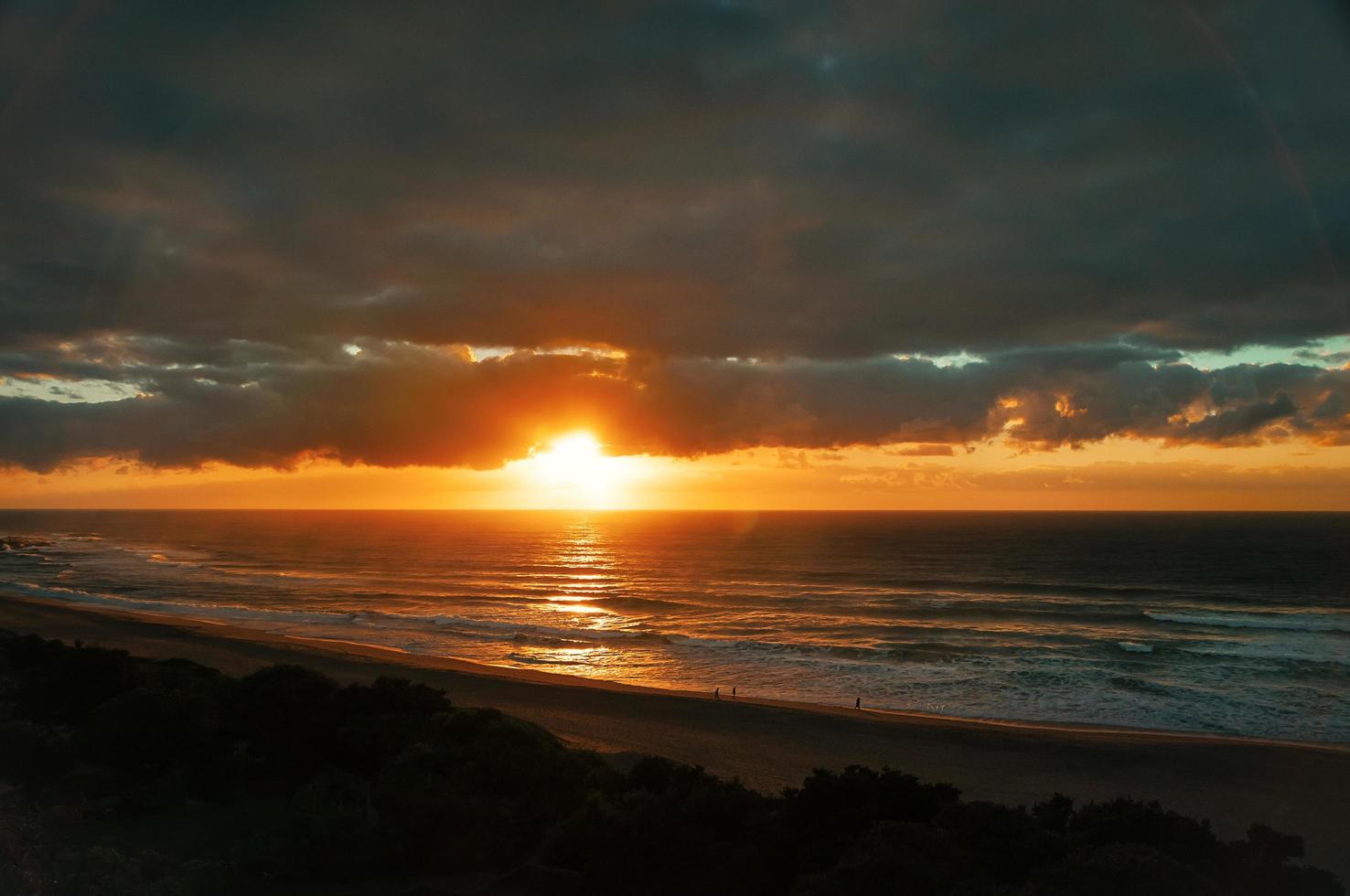 lever du soleil tôt sur la plage de l'océan, silhouettes de personnes, nuages dramatiques photo