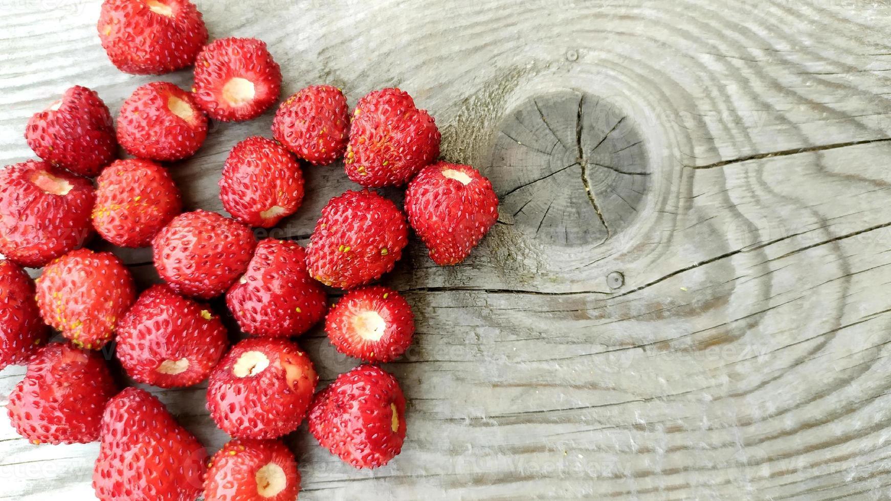 fraises sur un fond en bois. les baies rouges mûres se trouvent photo