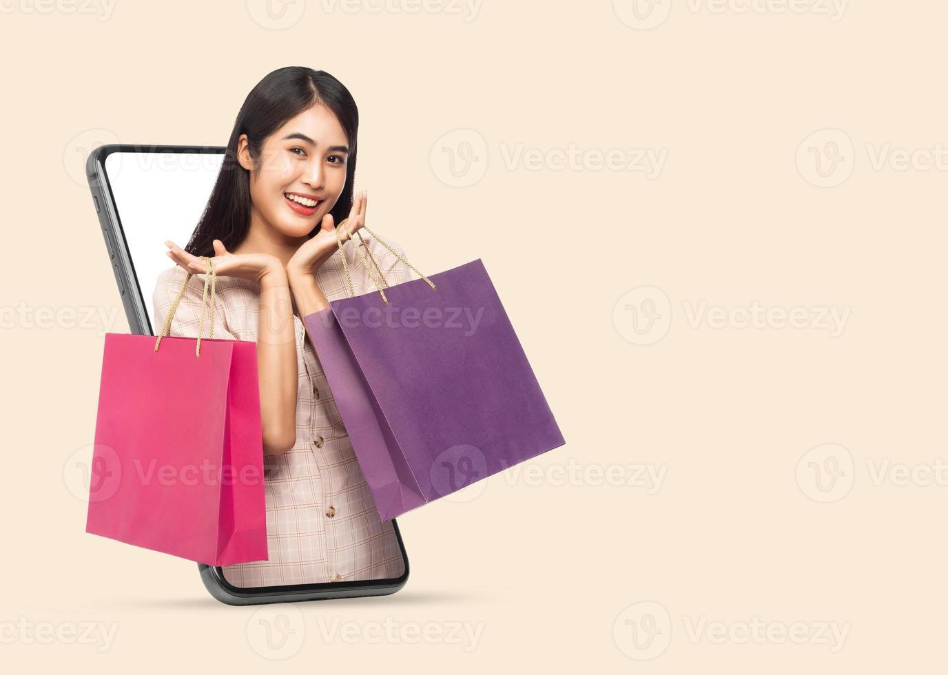 jeune femme tenant des sacs à provisions via smartphone photo