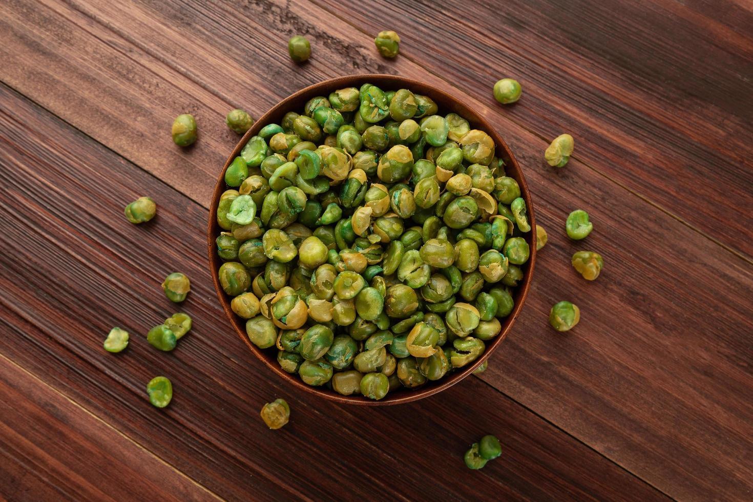 pois verts salés dans un bol en bois sur la table, collation saine photo