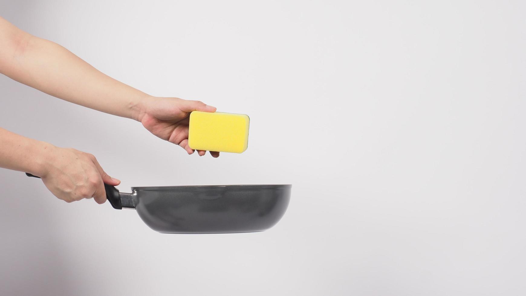 main de l'homme sur fond blanc nettoyant la poêle antiadhésive photo