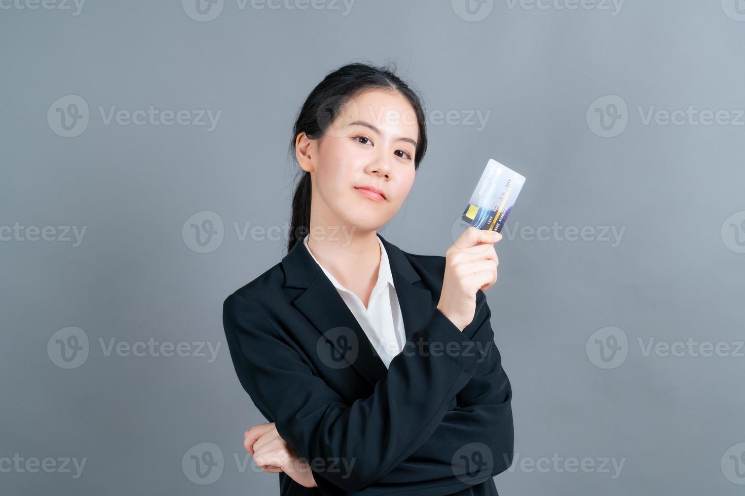 portrait d'une jolie jeune femme asiatique montrant une carte de crédit photo