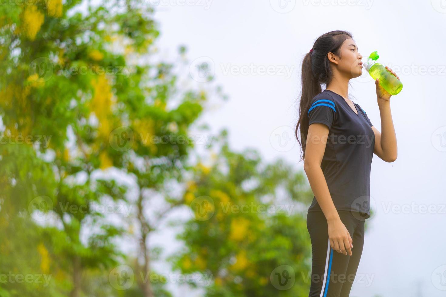 portrait de belle fille dans l'eau potable de vêtements de sport photo