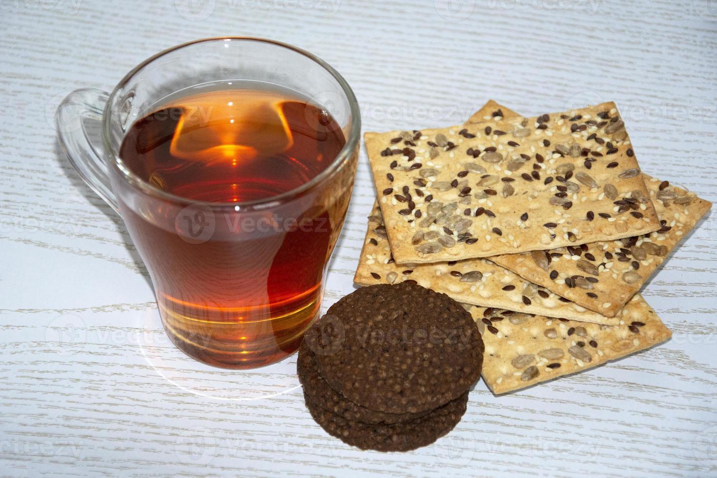 tasse en verre avec du thé chaud et des biscuits photo