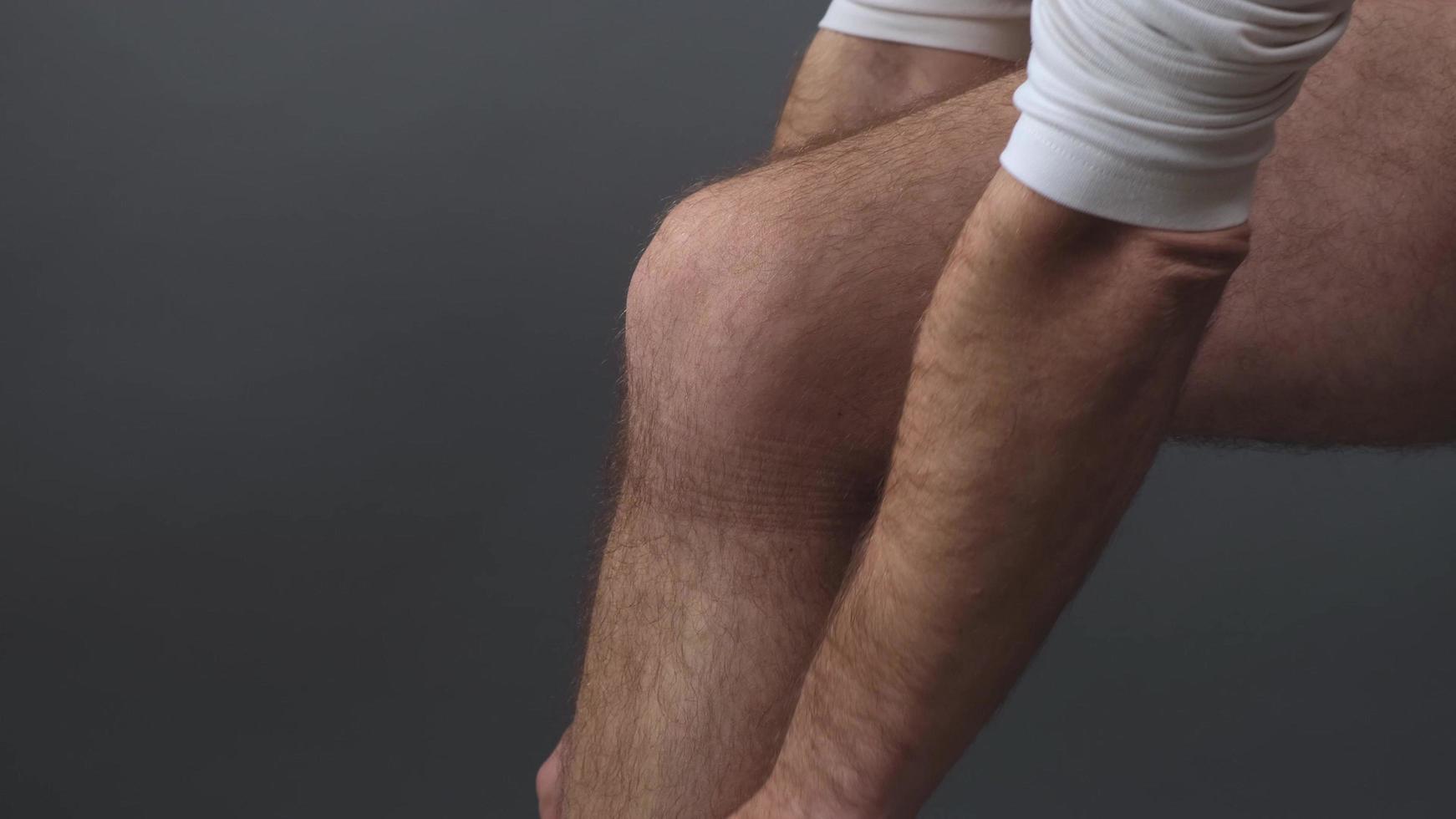 un homme met un pansement sur sa jambe quand les entorses photo
