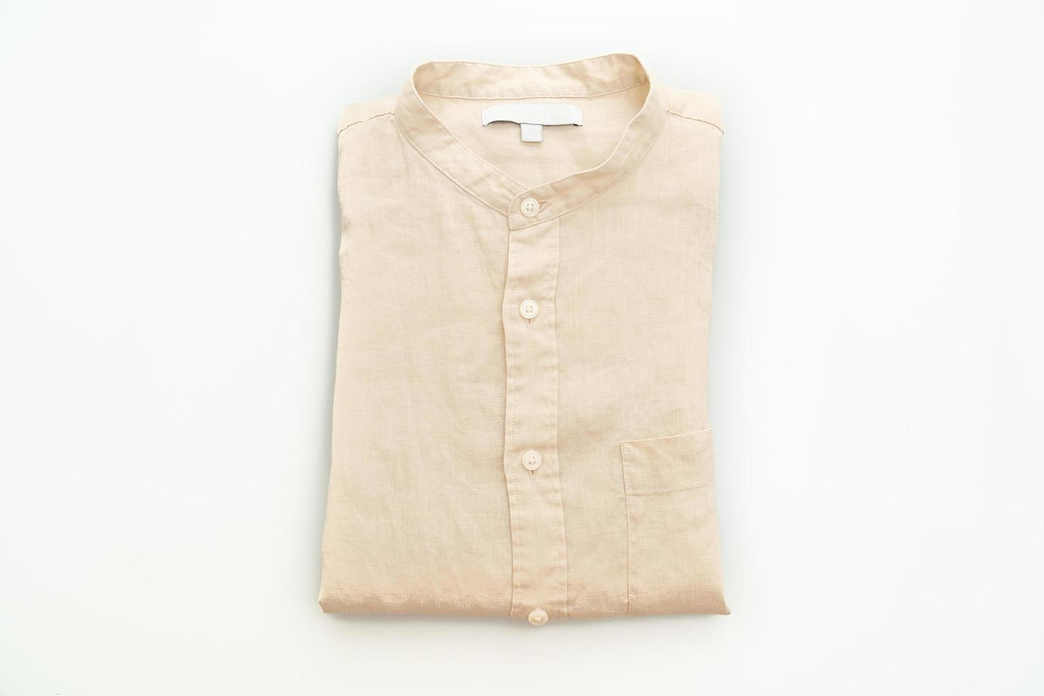 Chemise beige pliée isolé sur fond blanc photo