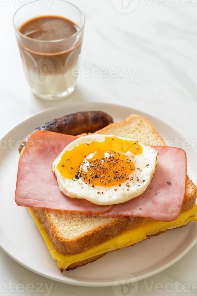pain fait maison fromage grillé garni de jambon et oeuf au plat avec saucisse de porc et café pour le petit déjeuner photo