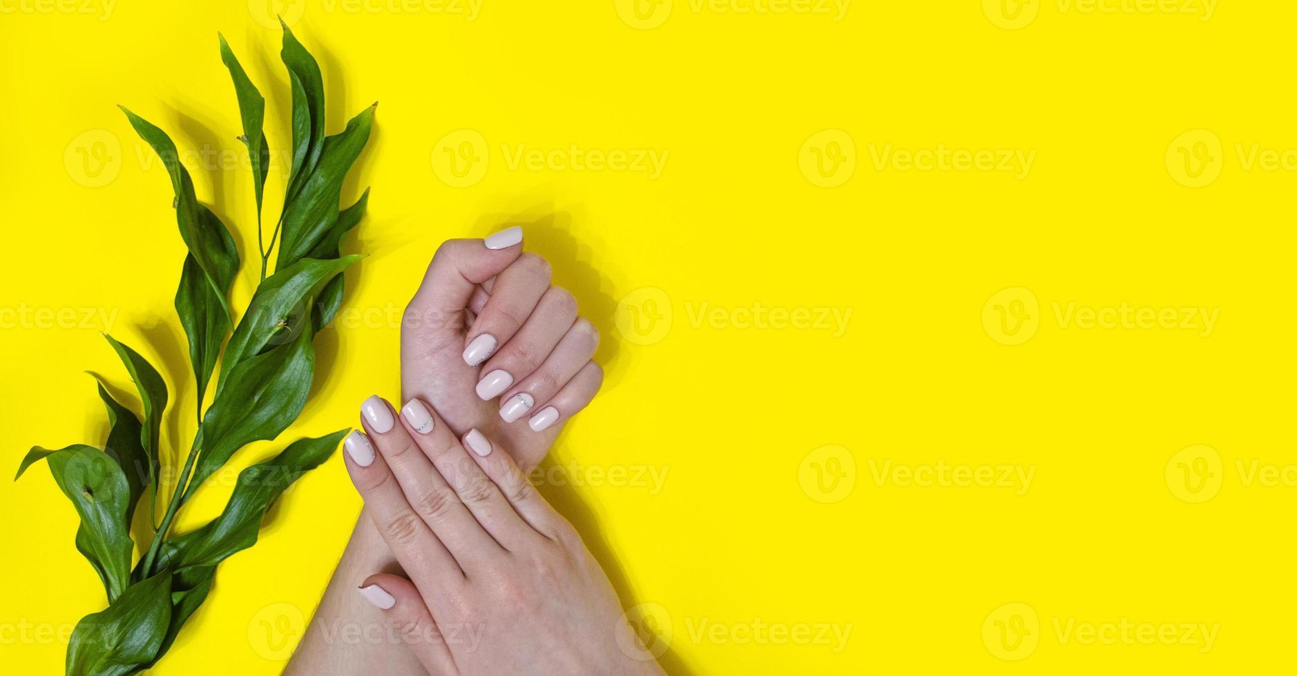 manucure féminine sur fond clair. jaune photo