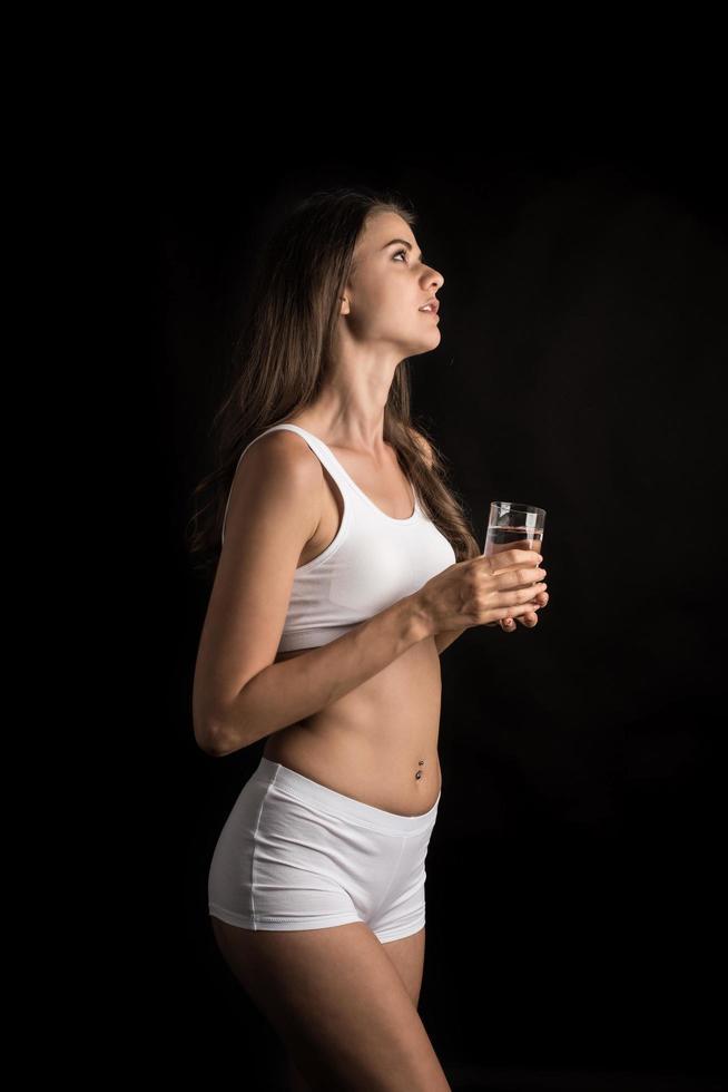 modèle de fitness féminin tenant un verre d'eau photo