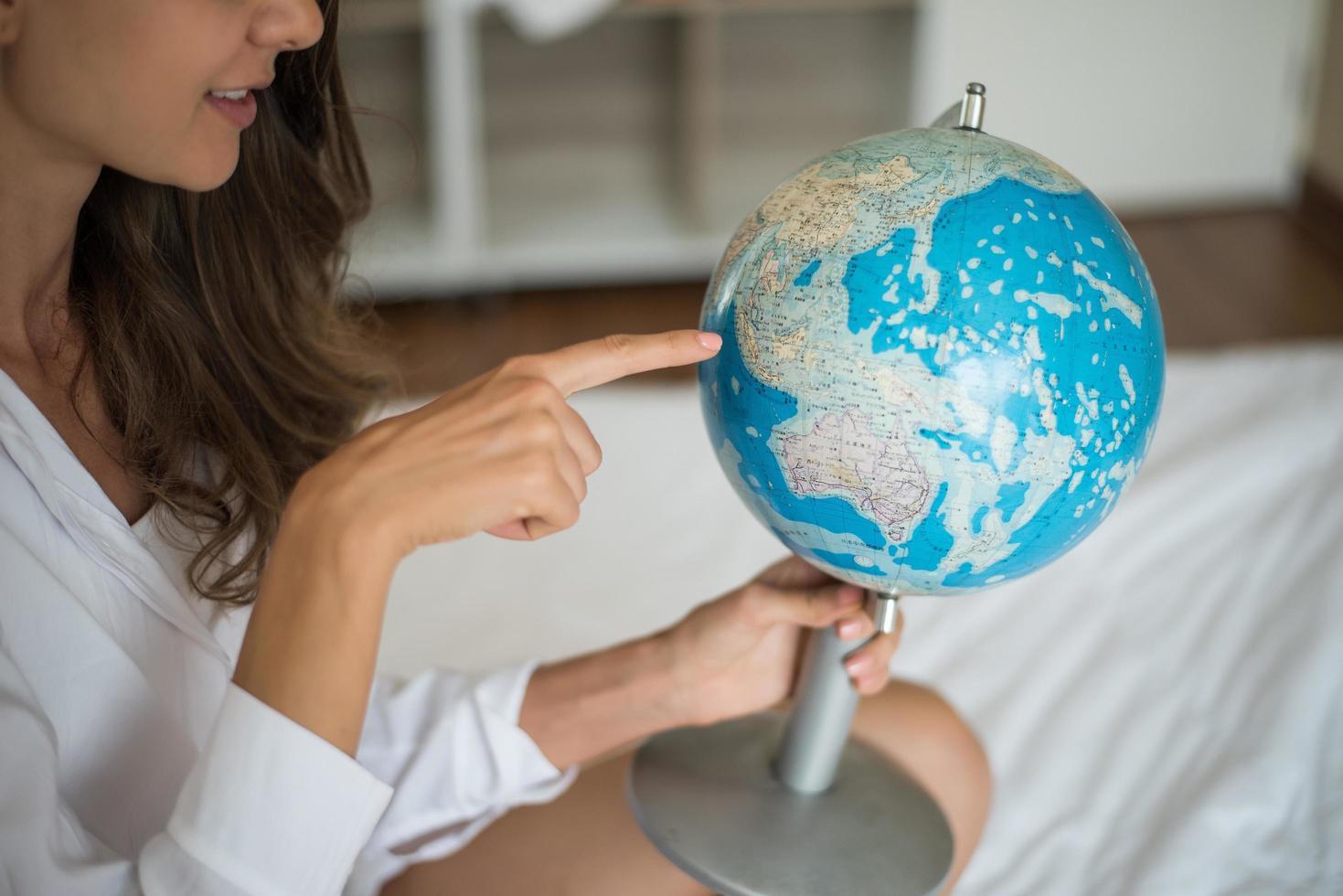 Pointer du doigt une femme vers la destination sur le modèle de boule de globe de carte du monde photo