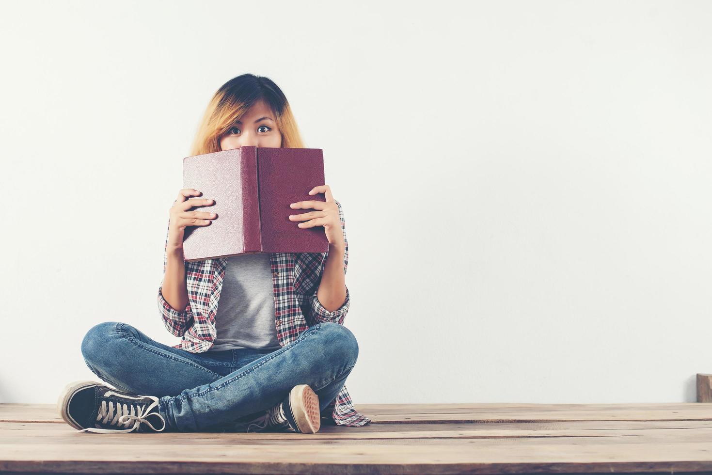 une jeune femme hipster a retiré le livre de son visage avec timidité. photo