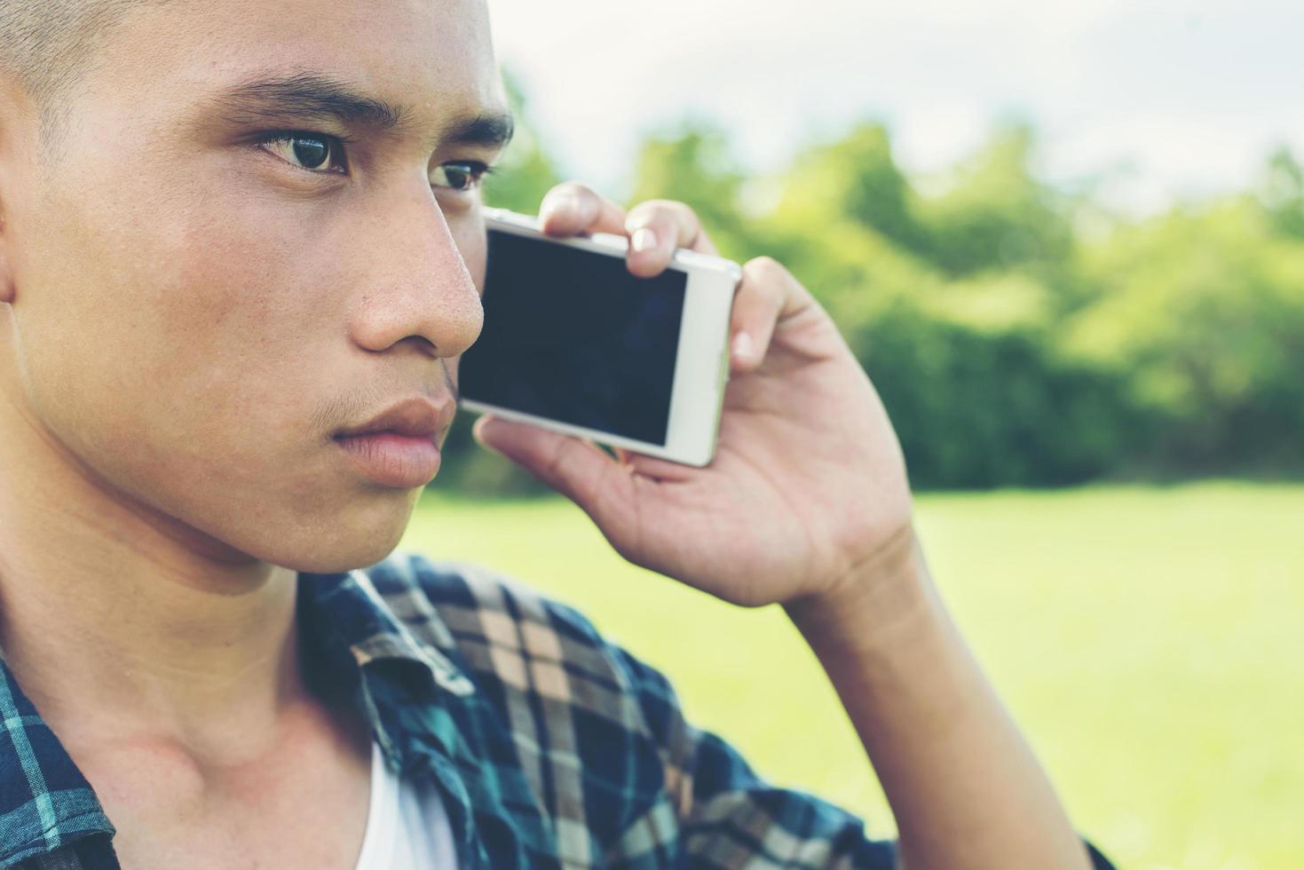jeune homme parlant au téléphone et debout sur l'herbe dans le parc. photo