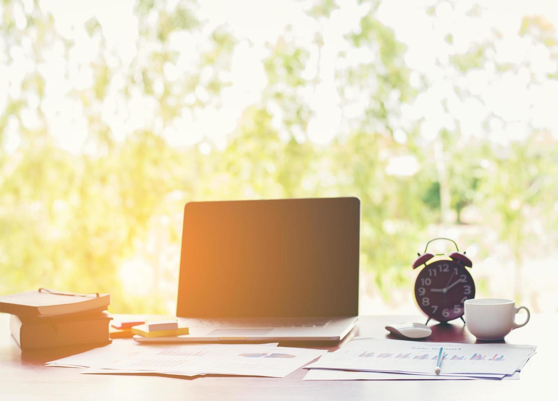 lieu de travail de bureau avec ordinateur portable sur table en bois contre les fenêtres. photo