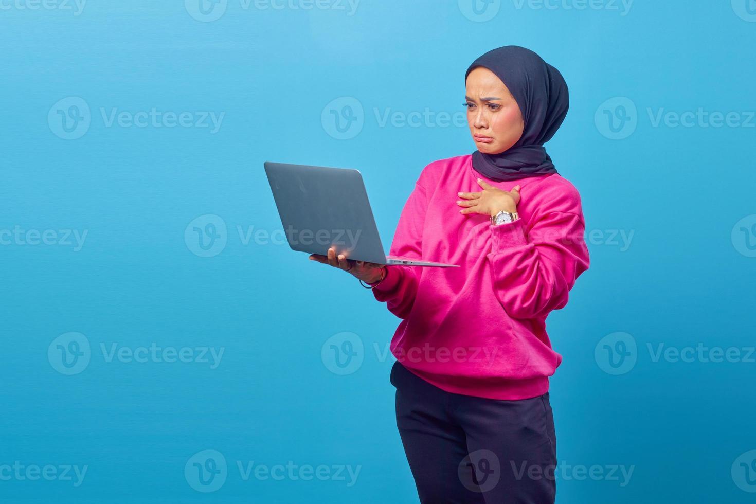 Portrait d'une fille surprise choquée debout et tenant un ordinateur portable photo