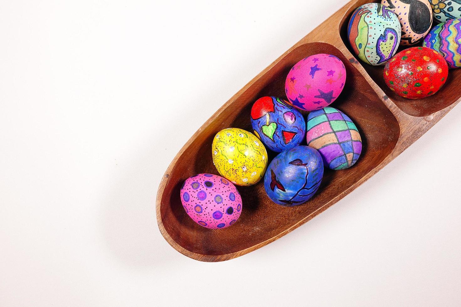 oeufs de pâques colorés pascals dans une assiette en bois photo