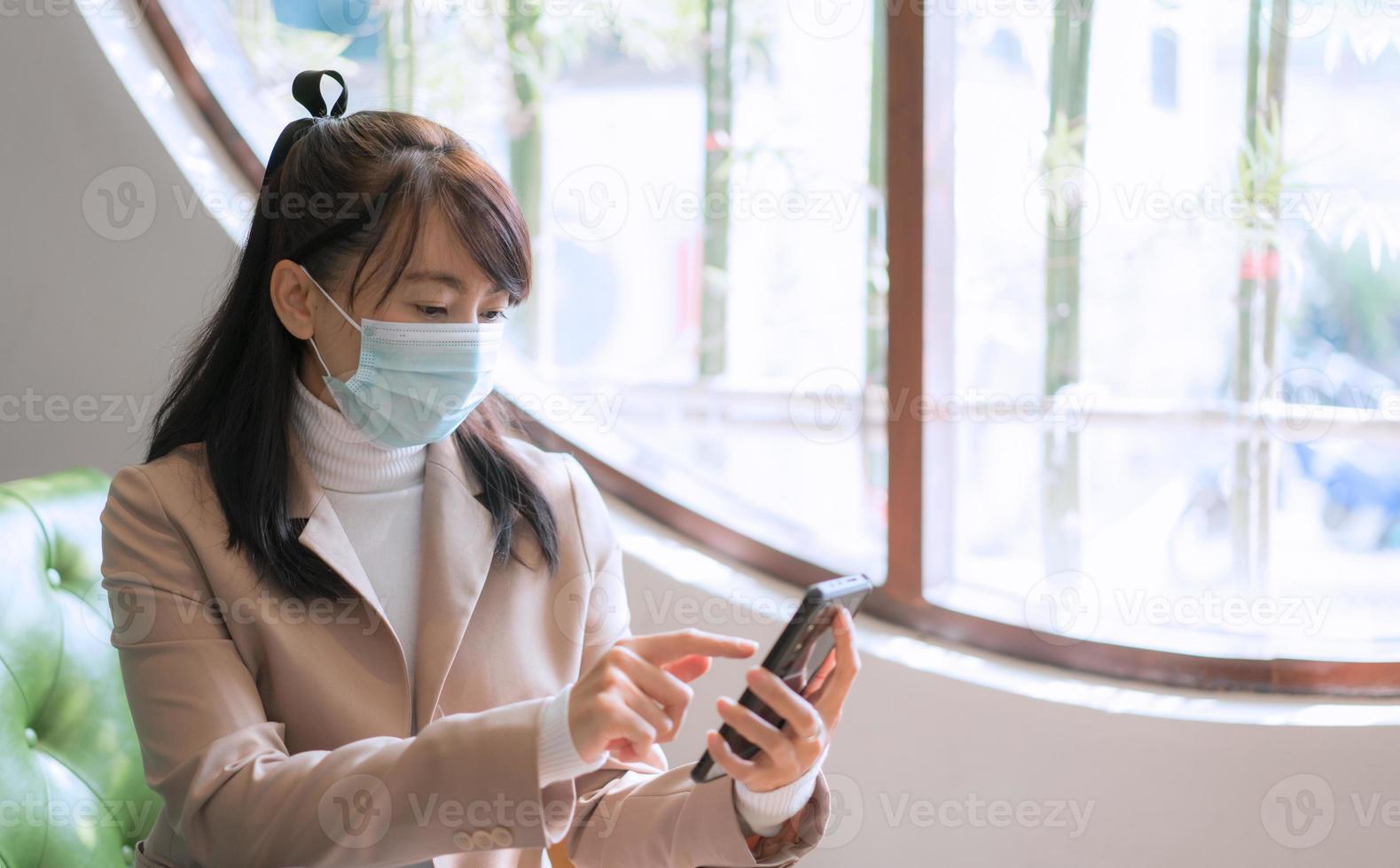 femme d'affaires portant un masque chirurgical et utilisant un smartphone photo