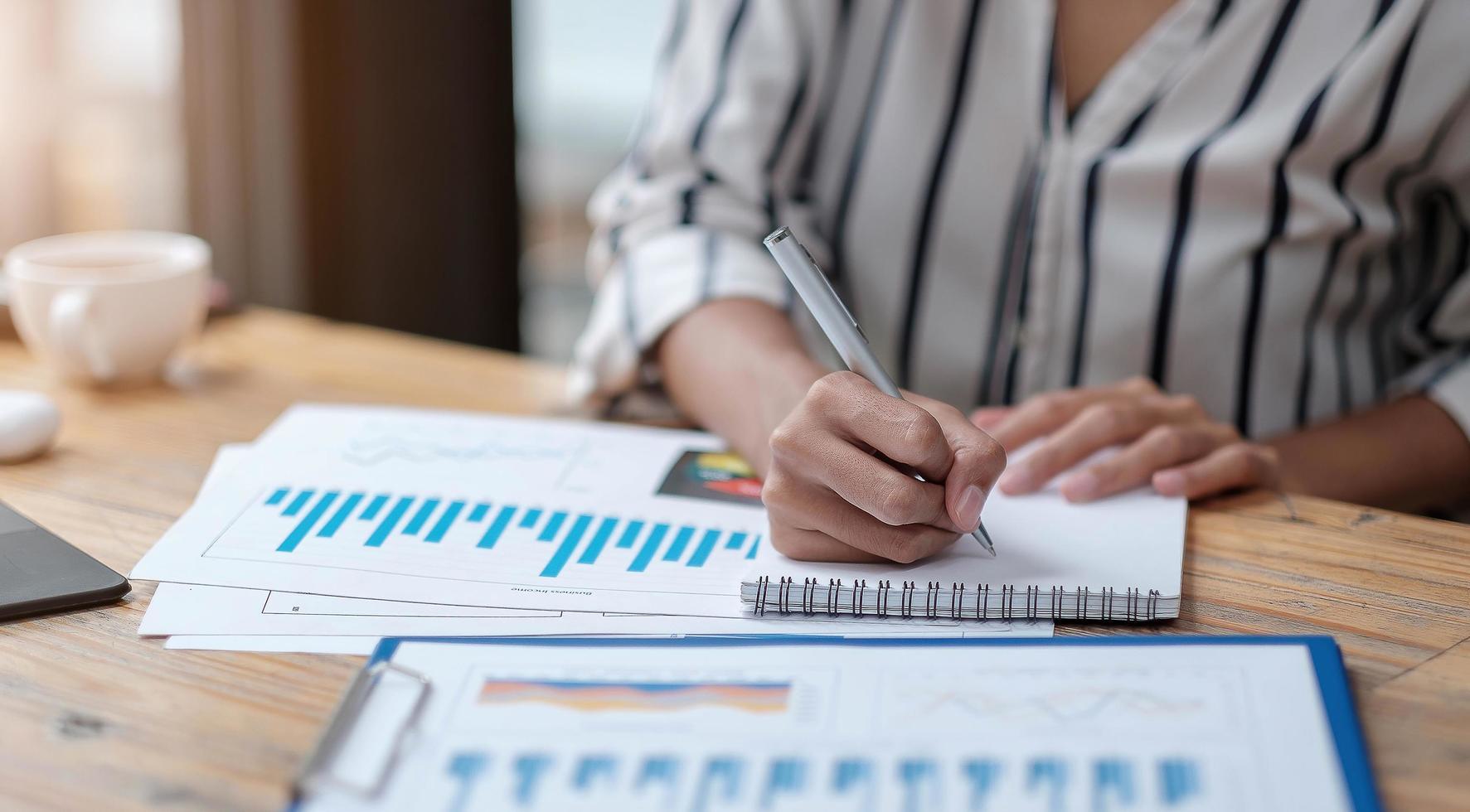 mains de gestionnaire de femmes d'affaires financières prenant des notes photo