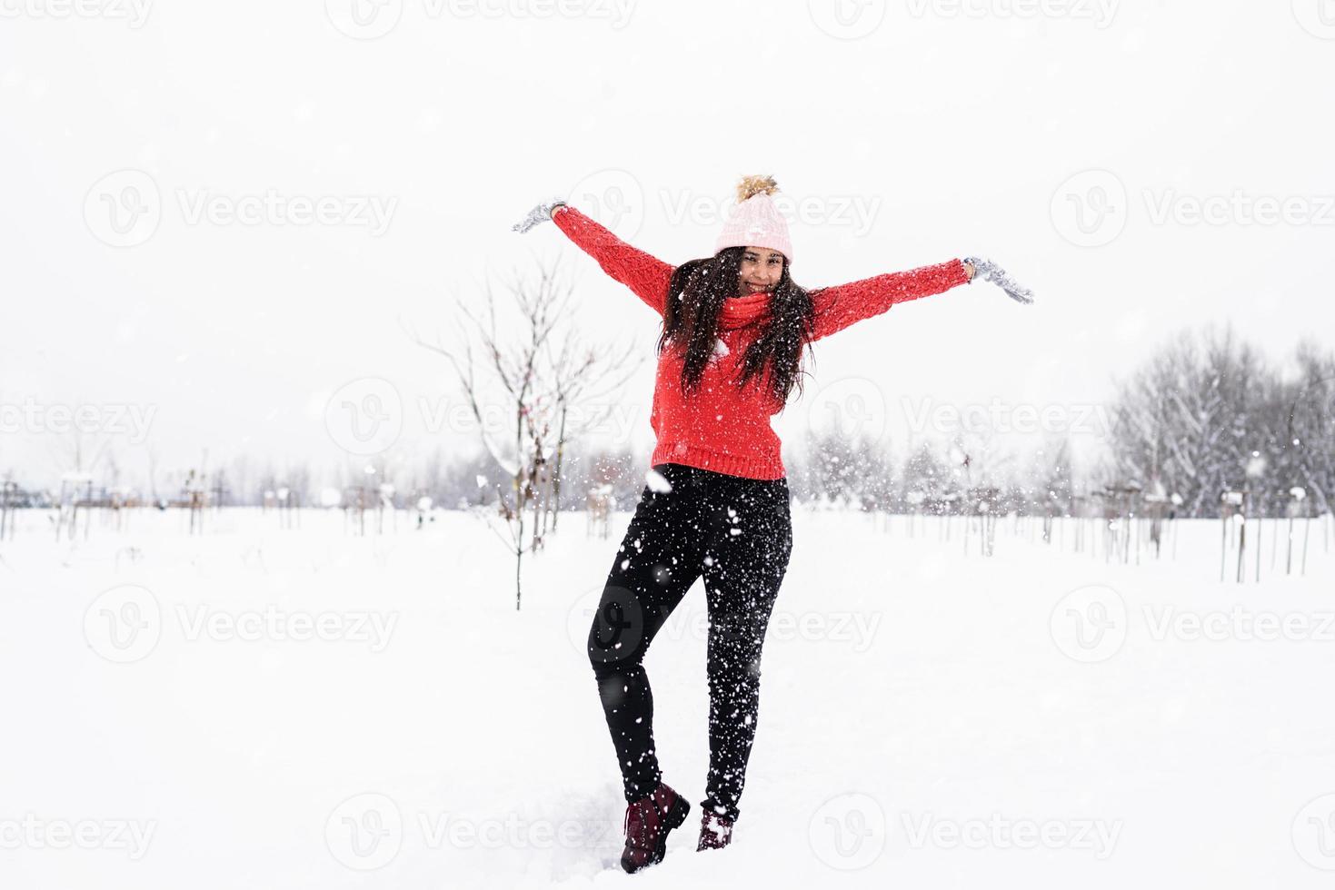 Jeune femme brune en pull rouge jouant avec de la neige dans le parc photo