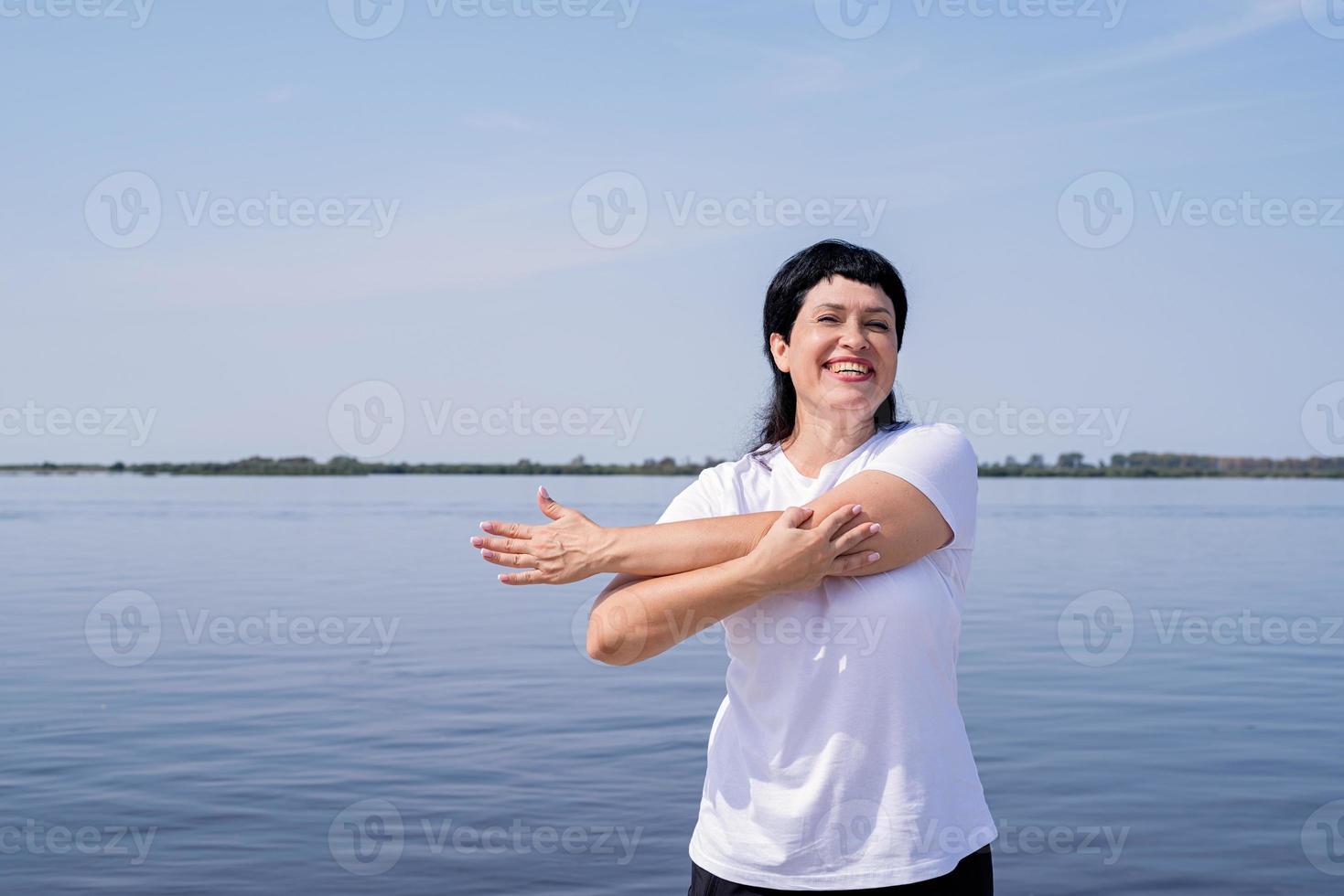 femme senior active et heureuse faisant des étirements près de la rivière photo