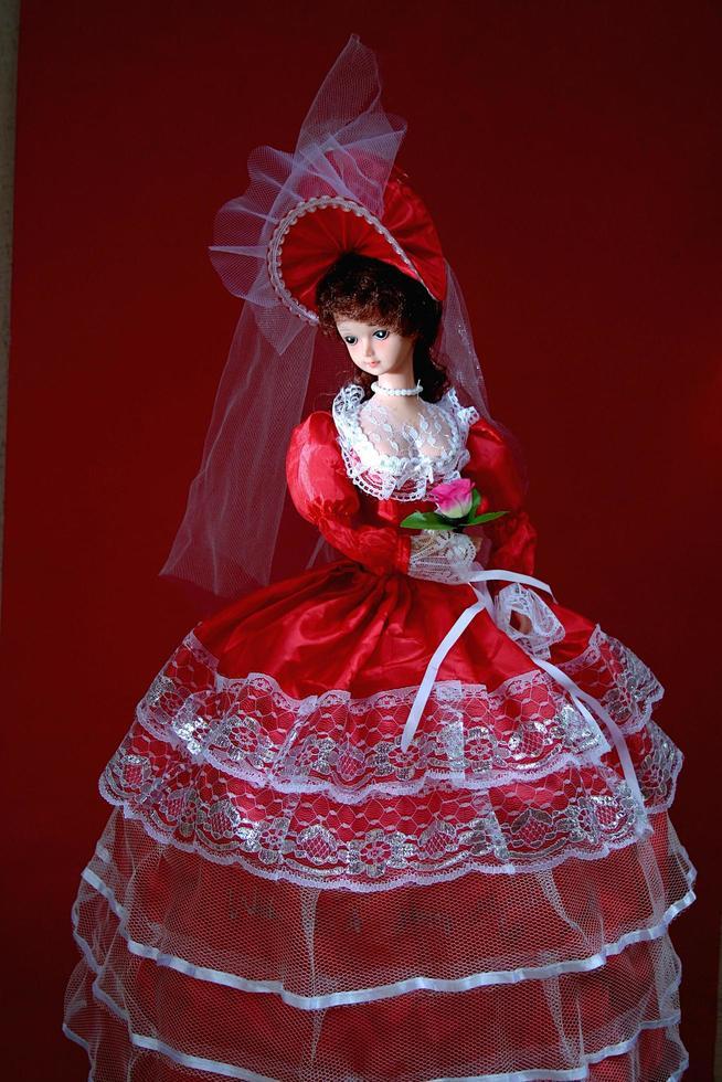 une poupée charmante et gracieuse avec une robe de mariée rouge vif photo