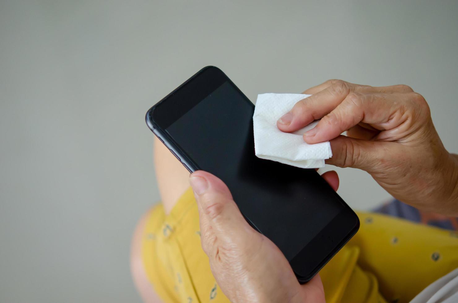 nettoyez votre téléphone portable avec de l'alcool pour éviter les germes. photo