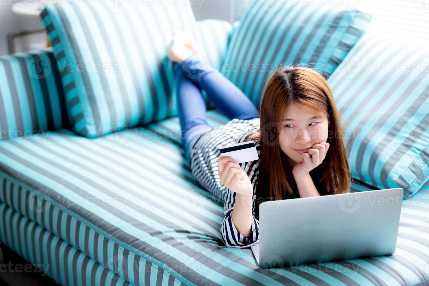 jeune femme asiatique couchée utilisateurs carte de crédit avec ordinateur portable. photo
