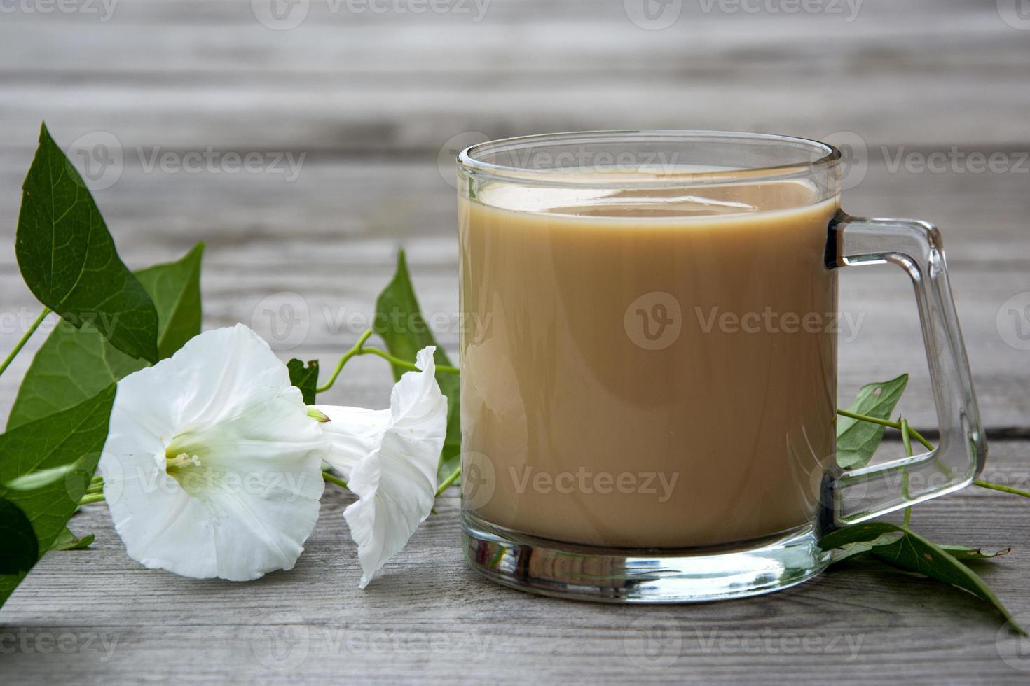 tasse avec du cacao et de la loche avec des fleurs blanches sur un fond en bois. photo
