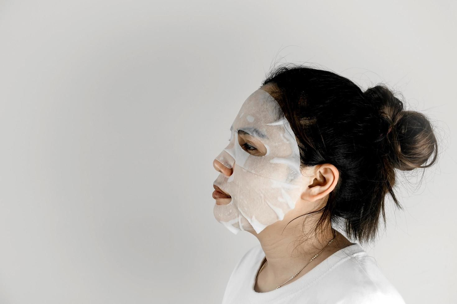 femme asiatique en t-shirt blanc et se couvrant le visage avec un masque en feuille. photo