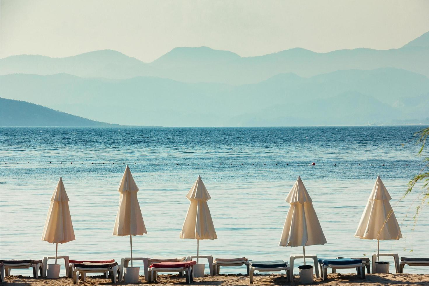 parapluies blancs, mer bleue et hautes montagnes à l'horizon photo