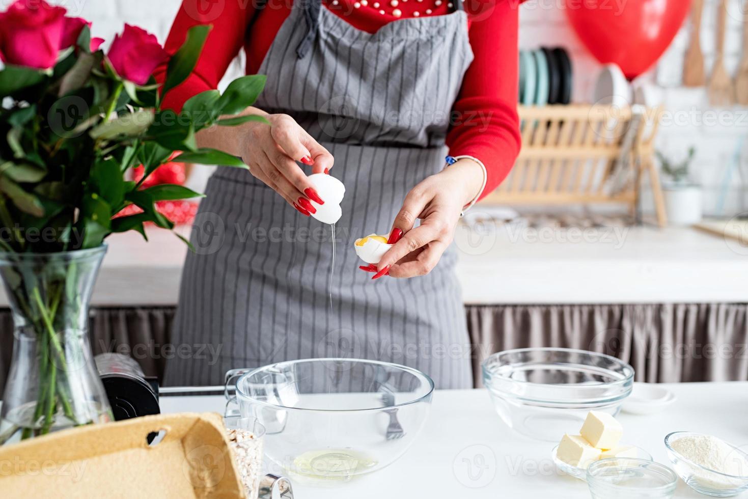 femme en robe rouge et tablier gris faisant la cuisine de la Saint-Valentin photo