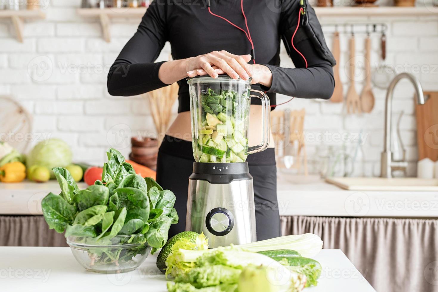 Jeune femme blonde souriante faisant un smoothie vert à la cuisine à la maison photo