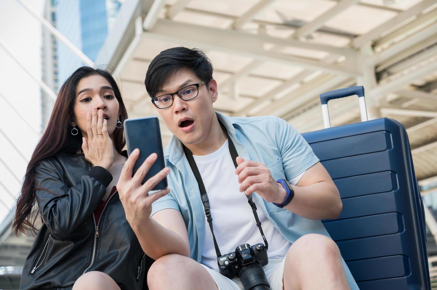 le couple aime le voyageur à la recherche d'un smartphone et se sent choqué. photo